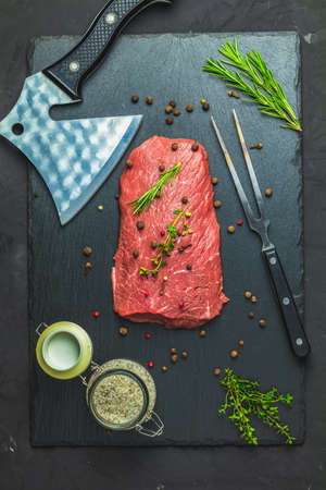 Fresh raw meat beef steak with ingredients for cooking spices, thyme on dark background, top view, copy space for you text