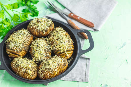 Delicious portion baked potatoes in black frying pan with pesto sauce, green onion, and cheese. Dish for dinner.