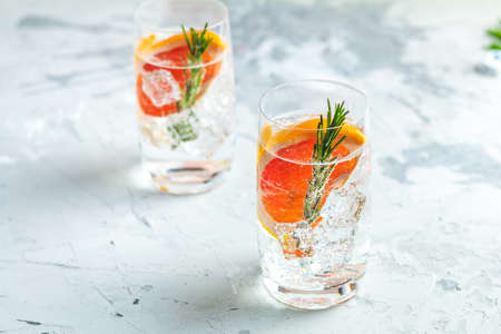 Alcoholic cocktail with grapefruit, soda, ice, gin and rosemary, light gray concrete table background, selective focus, shallow depth of the field. Stock Photo