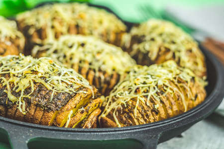 Delicious baked potatoes in black frying pan with pesto sauce, green onion, and cheese. Dish for dinner. Close up, shallow depth of the field