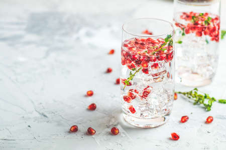 Festive drinks, gin and tonic pomegranate cocktail or detox water with ice. Selective focus, copy space for text, light gray concrete table surface.