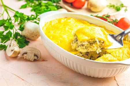 Loaded gratin, julienne or casserole from baked mushroom with chicken and cheese in bechamel sauce, white ceramic dish, shallow depth of the field, copy space for you text. Stock Photo