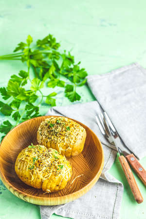 Delicious portion baked potatoes in wooden plate with green onion and cheese. Dish for dinner. Close up view.