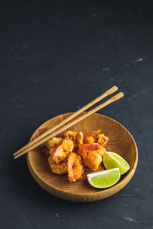 Fried Shrimps tempura with lime in wooden plate on dark concrete surface background. Copy space for you text. Seafood tempura dish served japanese or eastern Asia style with chopsticks. Stock Photo