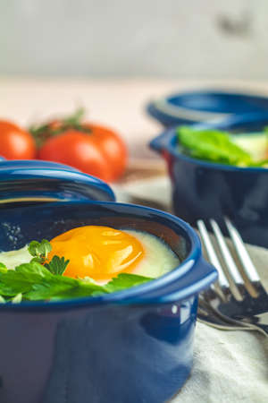 Eggs kokot cocotte french breakfast. Baked eggs  in blue ceramic baking molds. Portioned casserole from vegetables and eggs in Italian style. Close up, copy space.