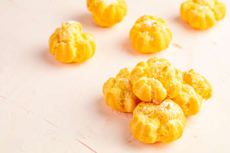 Delicious profiteroles with cream on pink or peach color concrete surface, copy space. Sweet food with copy space for you text. Stock Photo