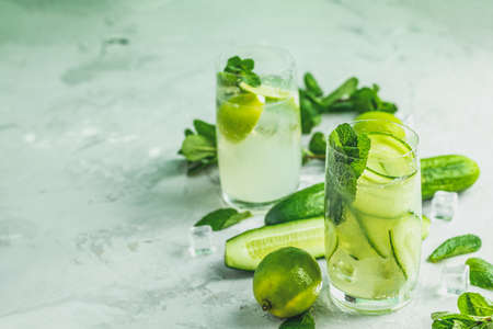 Detox cocktail of mint, cucumber and lemon and mojito cocktail with lime and mint in highball glasses on a gray concrete stone surface background. With copy space for your text