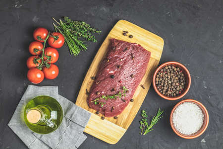 Fresh raw meat beef steak on wooden cutting board with ingredients for cooking spices, thyme, rosemary and tomatoes, dark background, top view, copy space for you text.