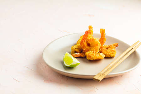 Fried Shrimps tempura in light plate on pink or peach concrete surface background. Copy space for you text. Seafood tempura dish of traditional asian cuisine. Stock Photo