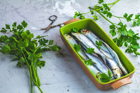 Sardines or baltic herring on green dish with parsley on light gray concrete table surface. Raw uncooked sea fish.