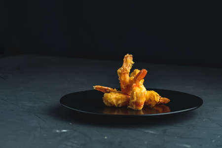 Fried Shrimps tempura in black plate on dark concrete surface background. Copy space for you text. Seafood tempura dish served japanese or eastern Asia style with chopsticks.