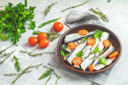 Sardines or baltic herring with rosemary, thyme, parsley,  tomatoes slices and spaces on ceramic plate on light gray concrete table surface. Raw uncooked sea fish, top view, copy space
