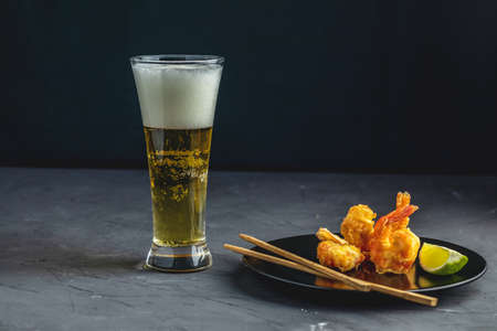 Fried Shrimps tempura with lime in black plate and glass of light beer on dark concrete surface background. Copy space. Seafood tempura dish served japanese or eastern Asia style with chopsticks Stock Photo