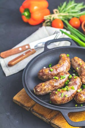 Fried sausage in a frying pan, with herbs and spices. Served on a wooden board with knife and fork, mustard, green onion, parsley and pickled cucumber, free space for your text.