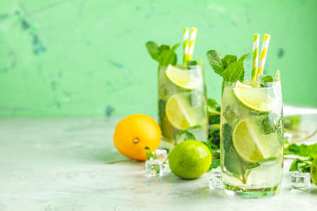 Two mojito cocktails with lime and mint in highball glasses on a gray and green concrete stone surface background. With copy space for your text