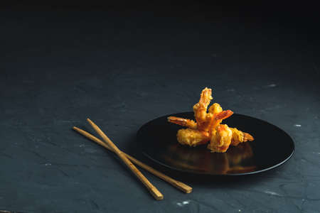 Fried Shrimps tempura in black plate on dark concrete surface background. Copy space for you text. Seafood tempura dish of traditional asian cuisine.