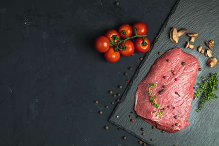 Fresh raw meat beef steak with ingredients for cooking spices, thyme, tomatoes and mushrooms on dark background, top view, copy space for you text.