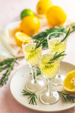 Traditional italian homemade lemon alcohol drink liqueur limoncello with pieces of lemon and rosemary herb on light pink, peach or coral color stone concrete surface Standard-Bild