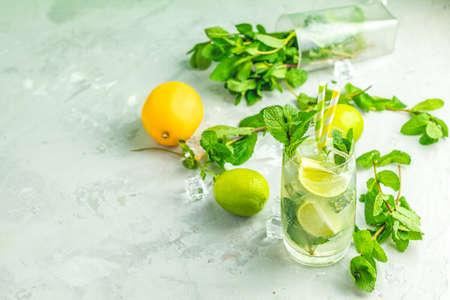 Mojito cocktail au citron vert et menthe en verre highball sur fond de surface en pierre de béton gris et vert. Avec espace de copie pour votre texte Banque d'images