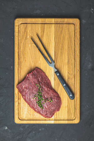 Fresh raw meat beef steak on wooden cutting board with  thyme, dark background, top view, copy space for you text.