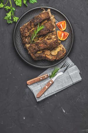 Delicious baked roast pork meat in black ceramic plate with garlic and spices. Dish for dinner. Top view, flat lay, dark concrete surface, copy space for you text