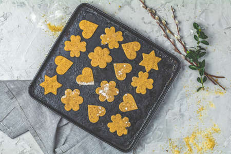 Culinary Spring or Christmas food background. Raw uncooked ginger cookies in baking dish on light gray concrete surface. View from above, copy space for text