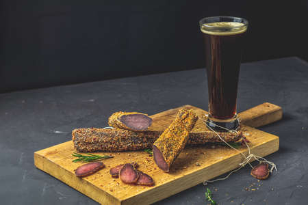 Dark beer in glass and Jerky, basturma, dried meat beef, meat smoked jerky with spices on wooden cutting board, black concrete surface table background.