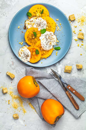 Delicious healthy fruit breakfast. Sliced persimmon with yogurt, chia seeds, brown sugar, pine nuts and fresh mint in blue plate on light gray concrete table surface background, top view, flat lay.