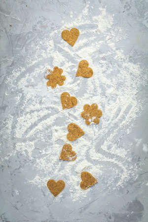 Raw homemade uncooked ginger cookies over light gray concrete surface. View from above, copy space for text, beautiful valentine day sweet food cooking card.