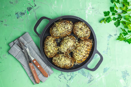 Delicious portion baked potatoes in black frying pan with pesto sauce, green onion and cheese. Dish for dinner. Top view, flat lay