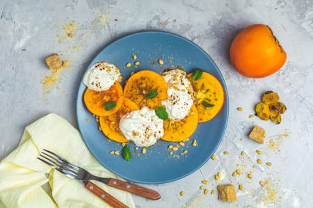 Delicious healthy fruit breakfast. Sliced persimmon with yogurt, brown sugar, pine nuts and fresh mint in blue plate on light gray concrete table surface background, top view, flat lay.