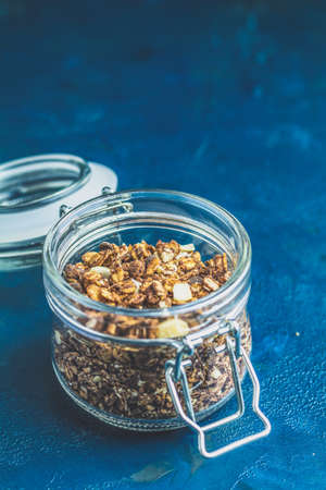 Open glass jar of organic granola with berries, coconut chips and seeds on a dark blue concrete table surface. Stockfoto