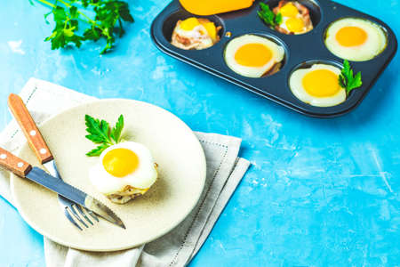 Baked eggs  in light plate and baking molds. Portioned casserole from bacon  and eggs in Italian style. Blue concrete table surface background. 版權商用圖片