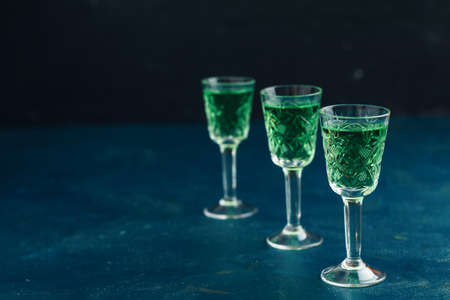 Traditional italian or czech liqueur or bitter with fennel. Three absinthe glass. Dark blue concrete table surface background, copy space for text. Stock Photo