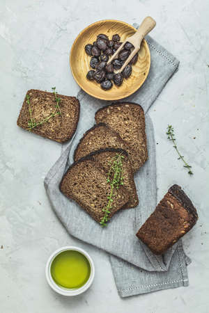 Whole wheat bread baked at home, bio ingredients, very healthy with seed and traditional greek italian appetizer dried olives on light gray concrete table surface. Stock Photo