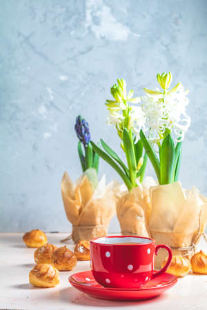 Red in white dotted cup of coffee with milk, delicious profiteroles with cream and white hyacinths on pink concrete surface. Happy Easter, Mothers day, birthday, wedding marriage festive background.