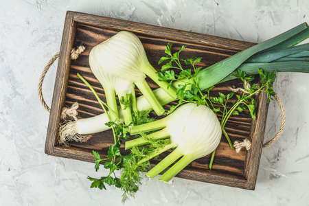 Fresh Florence fennel bulbs or Fennel bulb, leek and parsley in wooden box with dried grass on light gray concrete background. Healthy and benefits of Florence fennel bulbs.