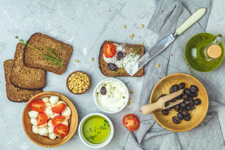 Whole wheat bread baked at home, very healthy with seed, bowl of cream cheese, mozarella, pine nuts and traditional greek italian appetizer dried olives on light gray concrete table surface. Stock Photo