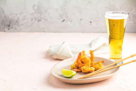 Fried Shrimps tempura with lime in light plate and glass of beer on pink or peach concrete surface background. Copy space. Seafood tempura dish served japanese or eastern Asia style with chopsticks