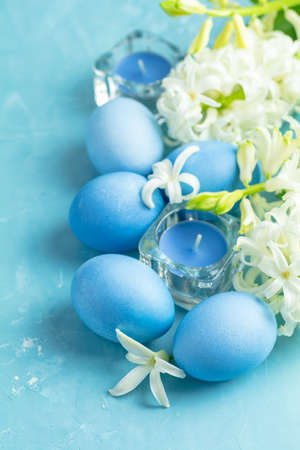Blue easter eggs, candles and white hyacinth on blue concrete table surface background, copy space for text. Festive background. Happy Easter greeting card.