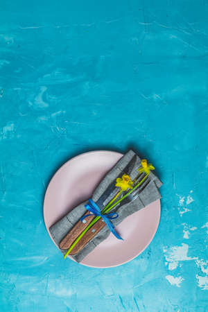 Empty pink plate and cutlery with daffodils on a napkin. Top view, blue concrete surface background, copy space for you text