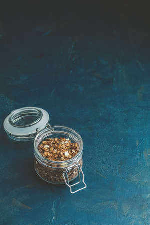 Open glass jar of organic granola with berries, coconut chips and seeds on a dark blue concrete table surface. Stock Photo