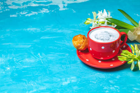 Red in white dotted cup of coffee with milk, delicious profiteroles with cream and white hyacinths on blue concrete surface background, copy space. Beautiful spring greeting card.