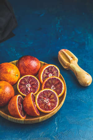 Sliced and whole Sicilian Blood oranges fruits in wooden plate and juicer over dark blue concrete table surface. Dark rustic style.