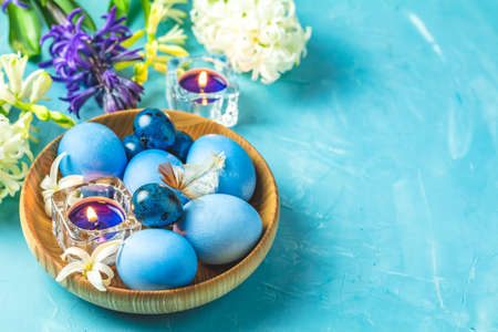 Easter greeting card with colored blue eggs, quail eggs and candles in wooden plate in front of white and blue hyacinths over blue concrete surface background. Happy Easter festive background