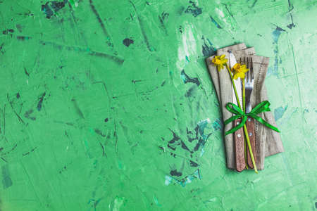 Cutlery with daffodils on a napkin. Top view, green concrete surface background, copy space for text