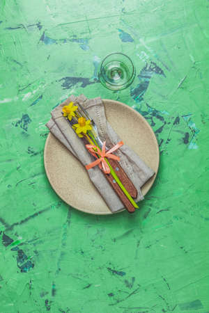 Empty beige plate and cutlery with daffodils on a napkin. Top view, green concrete surface background, copy space for text