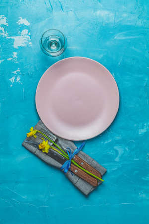 Empty pink plate and cutlery with daffodils on a napkin. Top view, green concrete surface background, copy space for text
