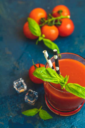 Red cocktail with tomato juice between tomatoes, fresh basil and ice. Delicious tomato bloody mary cocktail on dark blue concrete table.