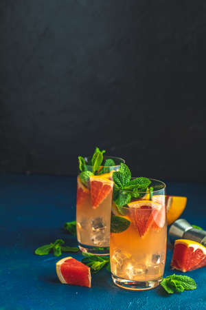 Grapefruit and mint gin tonic cocktail, refreshing drink with ice. Cold summer citrus refreshing drink cocktail or beverage with ice on dark blue concrete surface close up. 写真素材